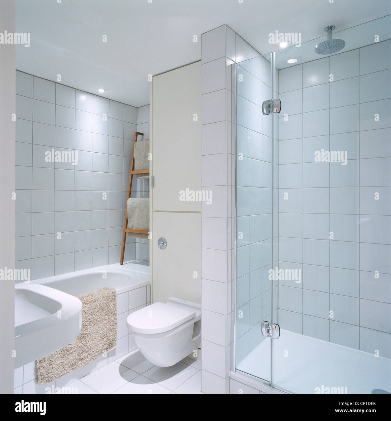 A modern white bathroom with tiled walls and floor, shower, toilet ...