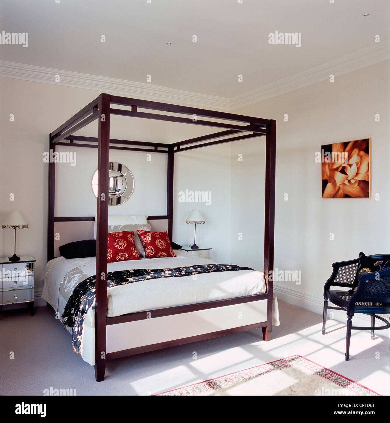 A modern white bedroom with four poster bed, silver chest of drawers, black wicker chair - Stock Image