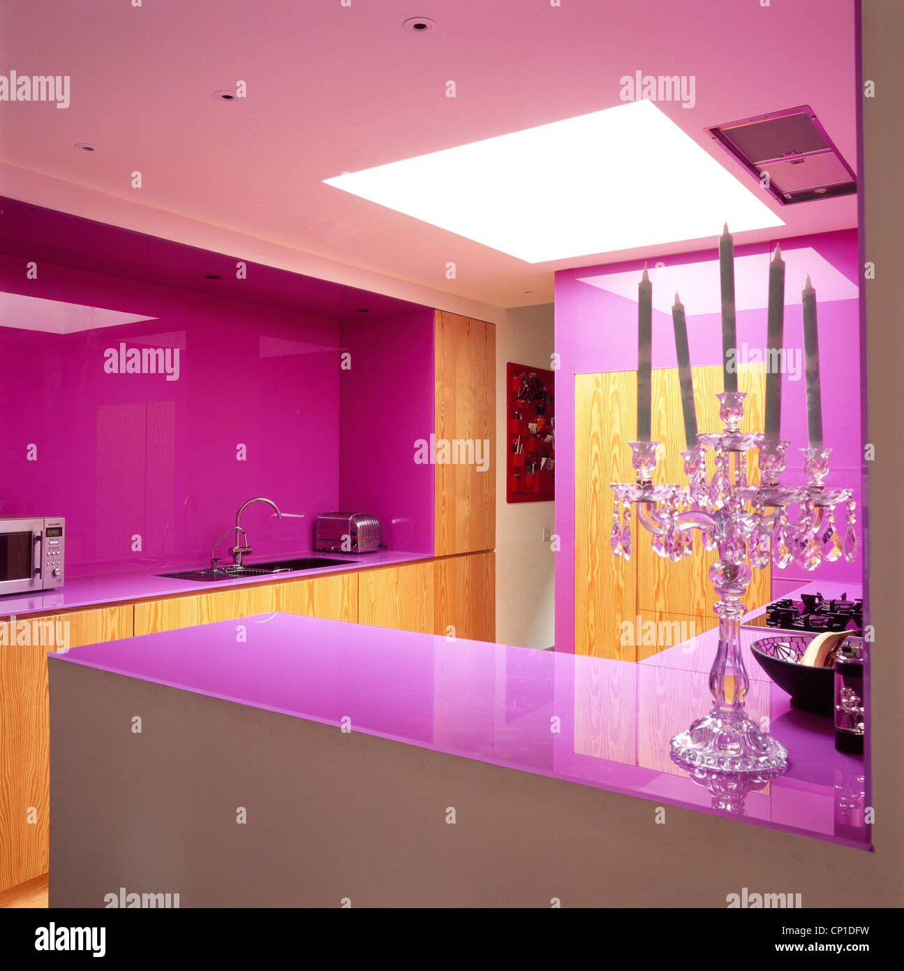 A modern pink kitchen with wooden units and purple work tops with a glass candelabra holder in the foreground. Stock Photo