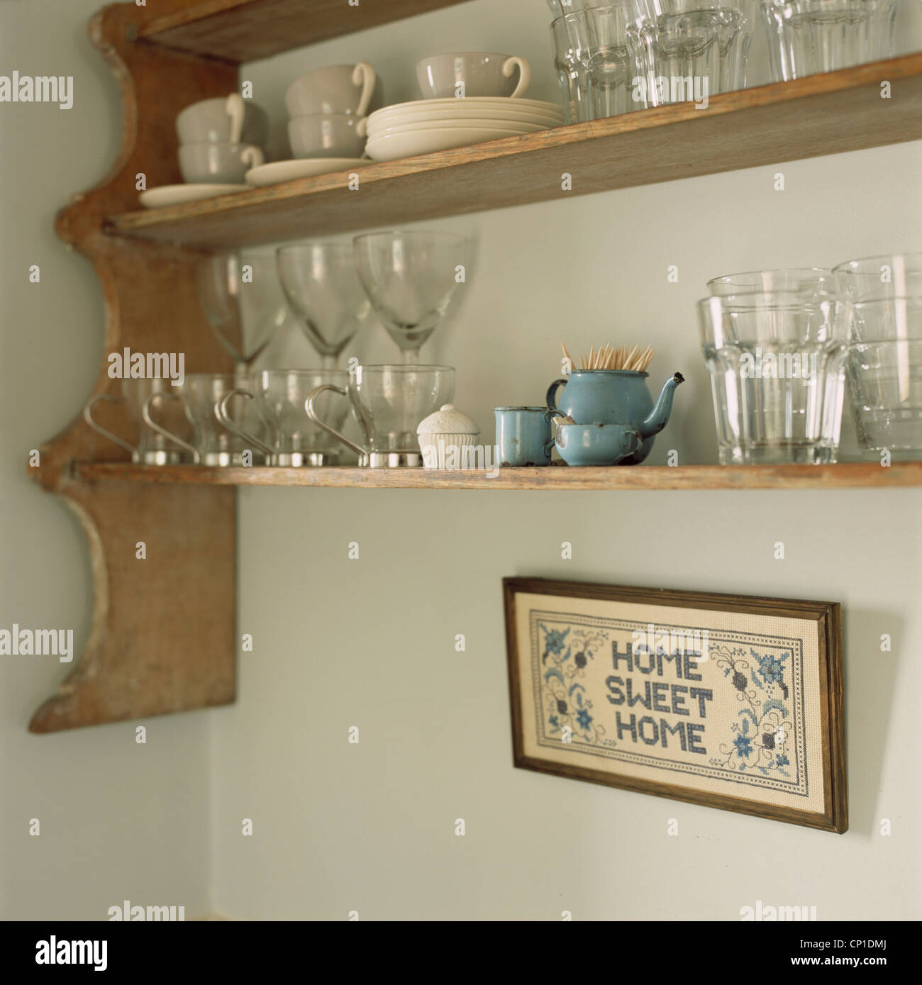 Tableware And Glassware On Wall Mounted Wooden Shelving Unit