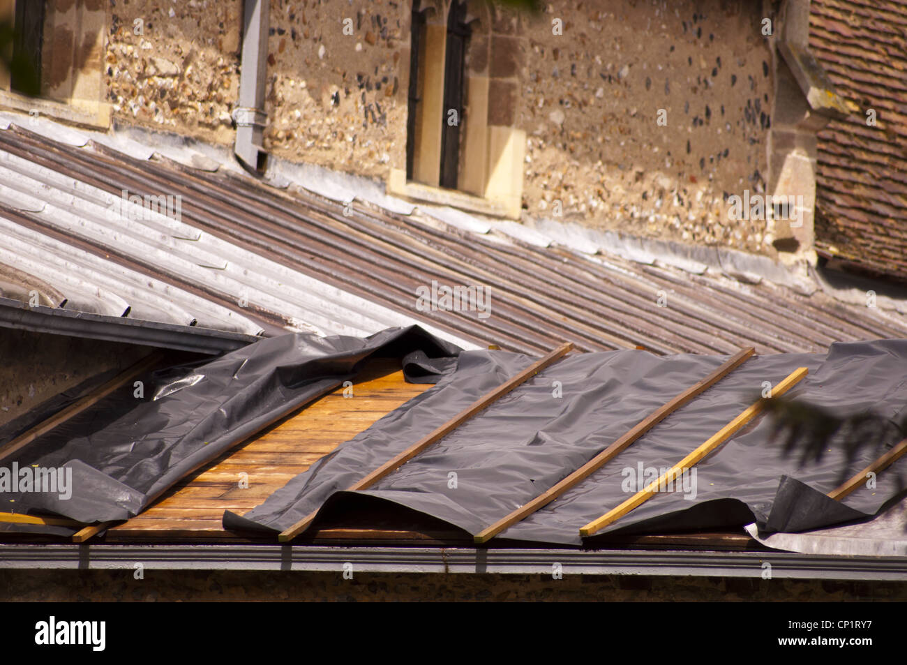 Plastic sheet covering church roof after thieves stole lead - Stock Image