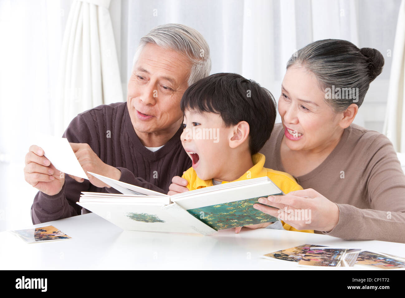 Grandparents and grandson looking through family album - Stock Image