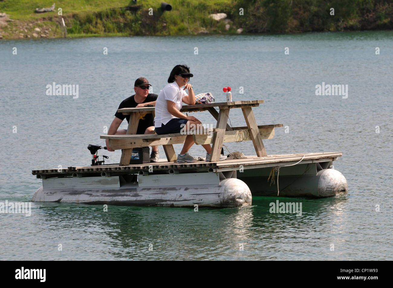 A couple cross a lake on a floating picnic table stock photo a couple cross a lake on a floating picnic table watchthetrailerfo
