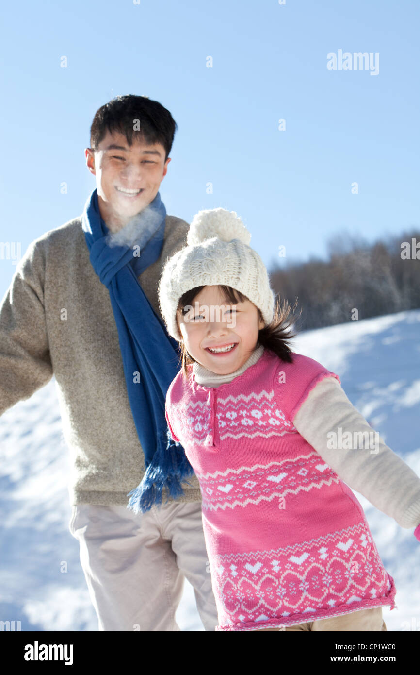 Father playing with daughter in snow - Stock Image