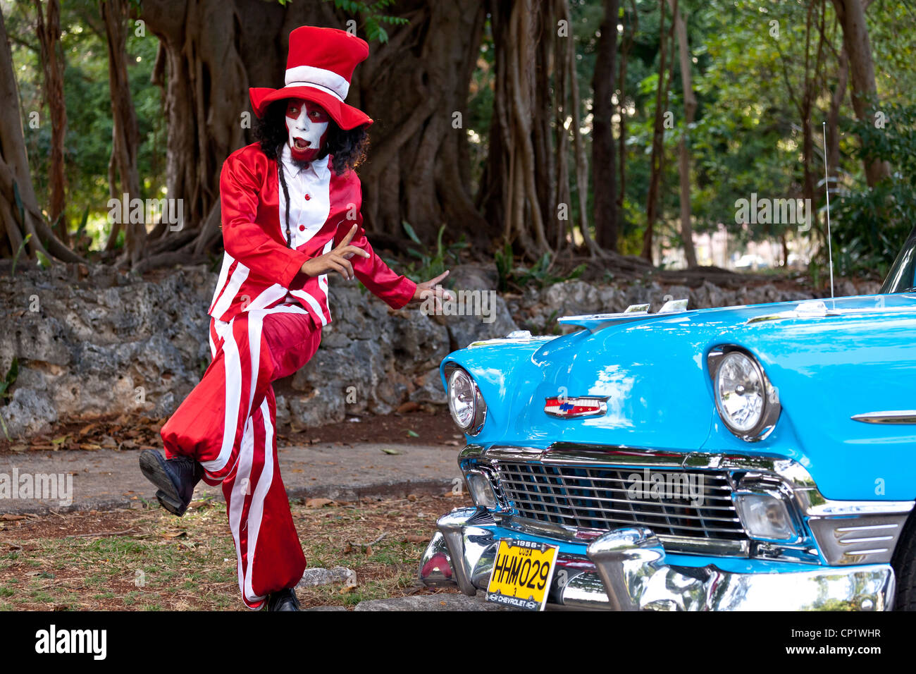 A Cuban Mime strikes a pose in front of a restored 1955 Chevy BelAir - Stock Image