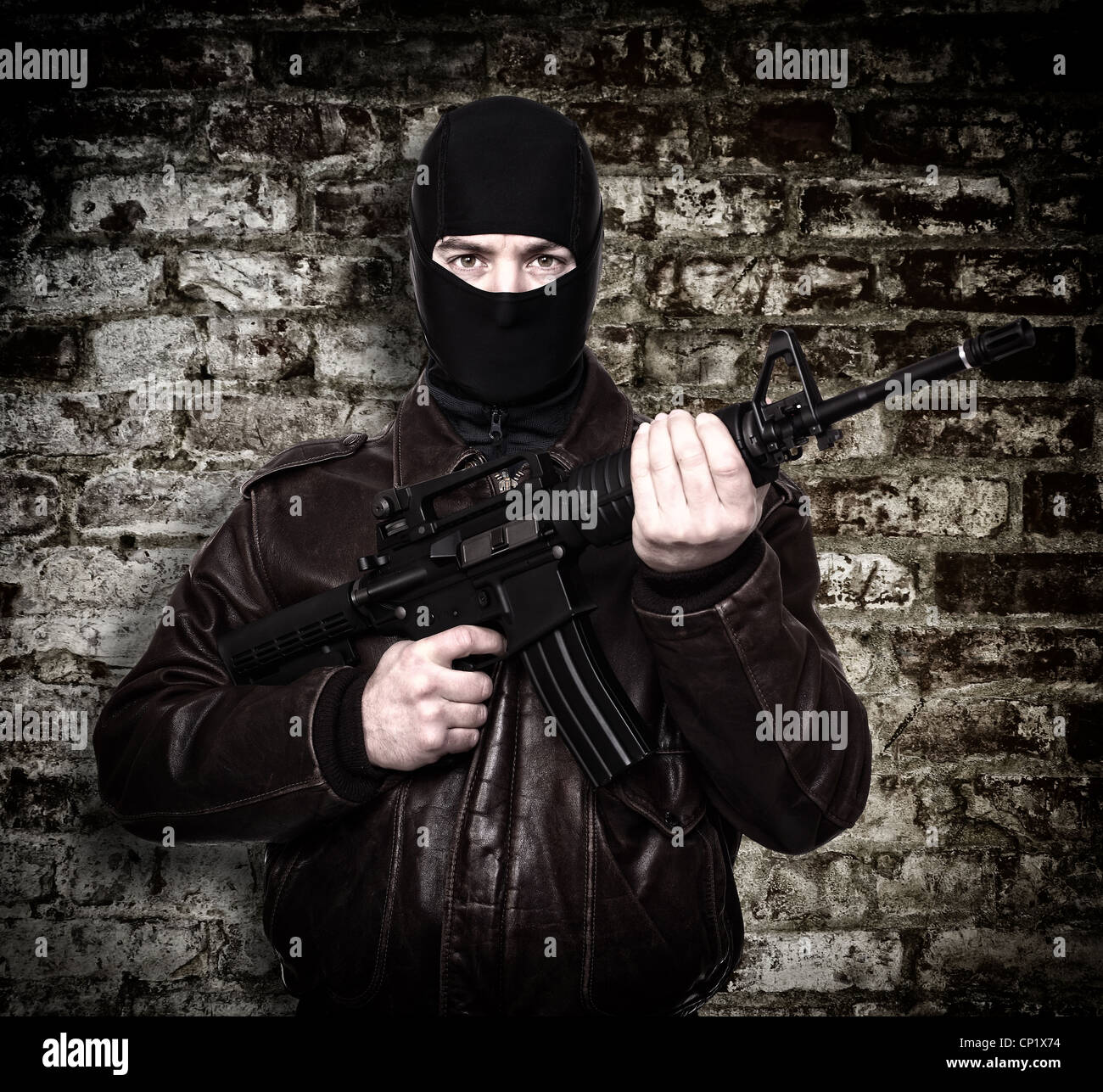 portrait of terrorist with automatic rifle - Stock Image