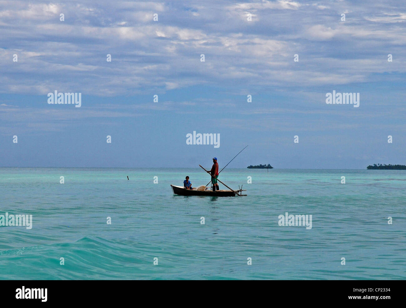 Man and son fishing from a small wooden canoe in a shallow lagoon, Aitutaki, Cook Islands,South Pacific. - Stock Image