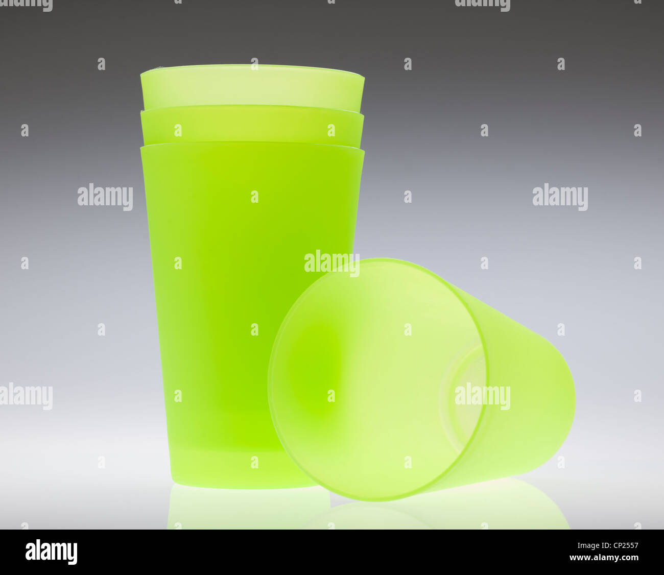 Four green plastic beakers - Stock Image