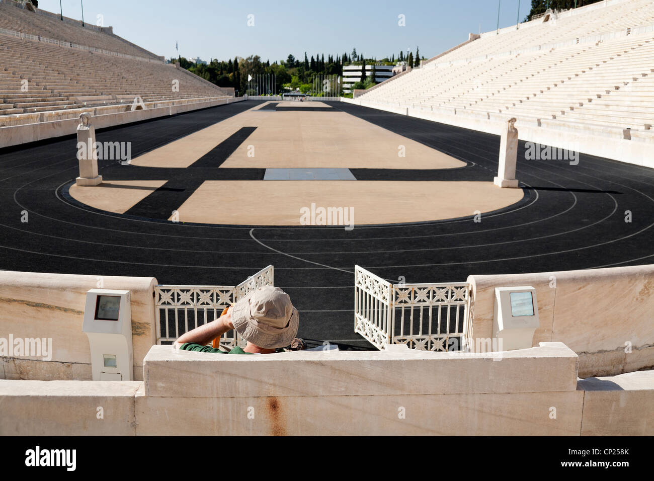 Tourist sit in the stands of the Panathenaic stadium and listen the audio tour. Athens, Greece. Stock Photo
