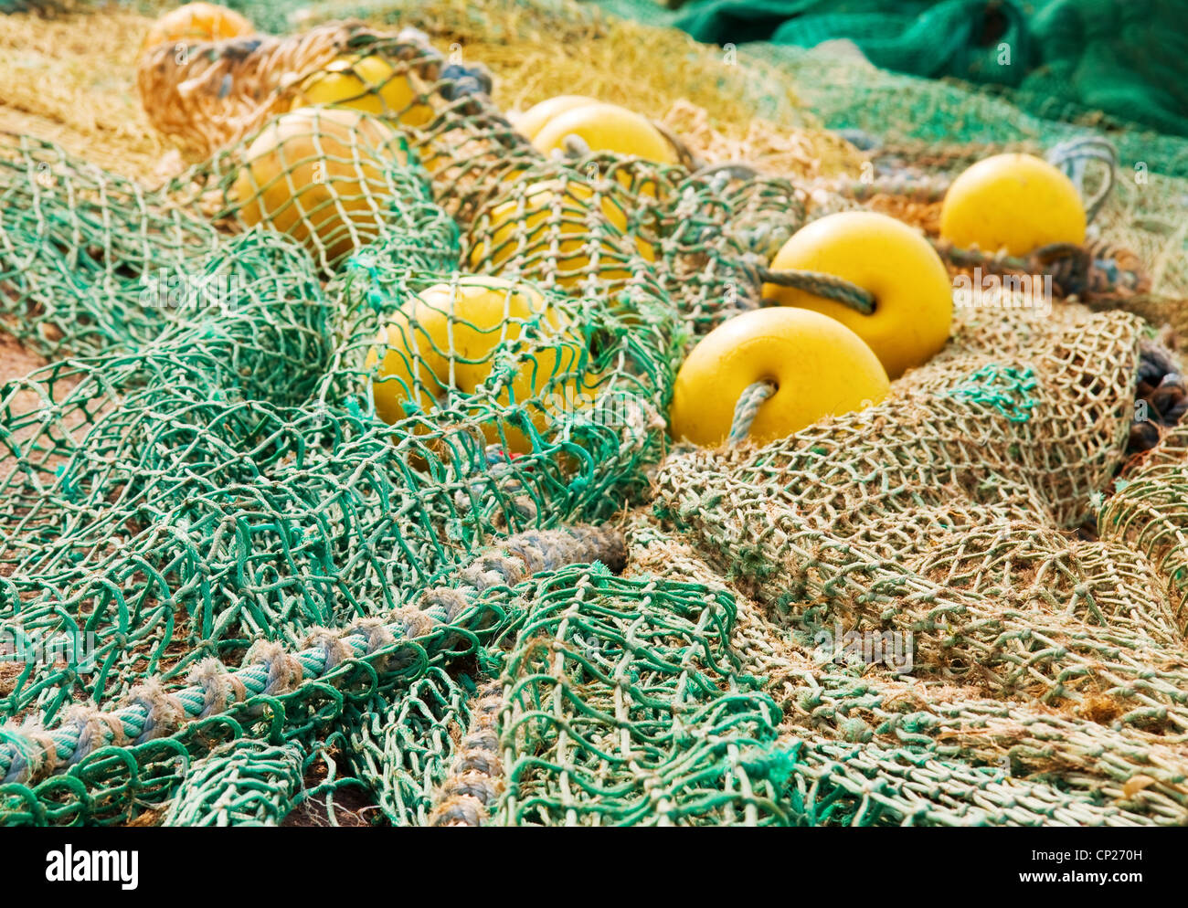 Colorful nets, coil of ropes and yellow floats used by fishermen for deep sea fishing. - Stock Image