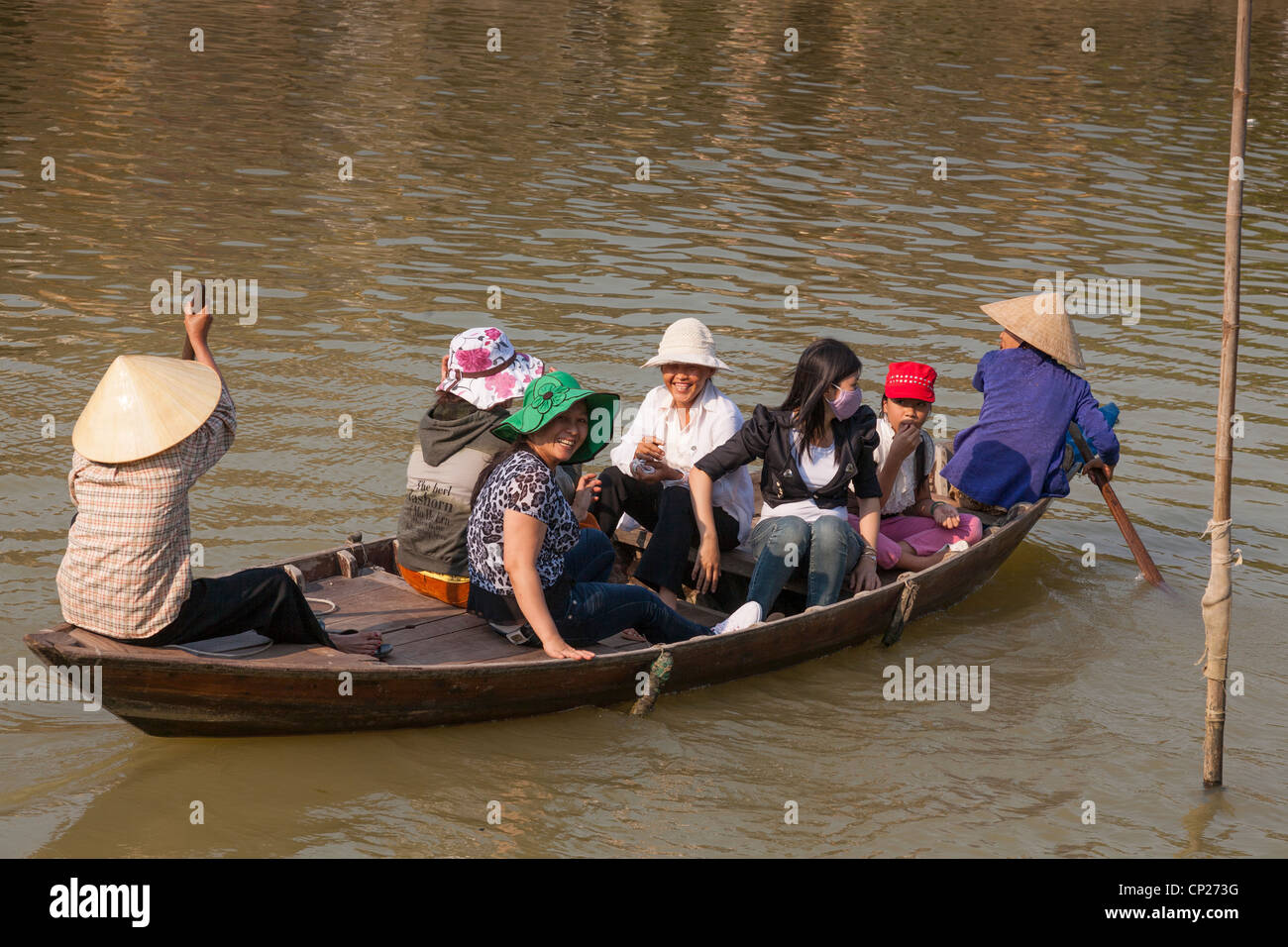 Women travelling in a small wooden boat, Hoi An, Quang Nam province, Vietnam - Stock Image