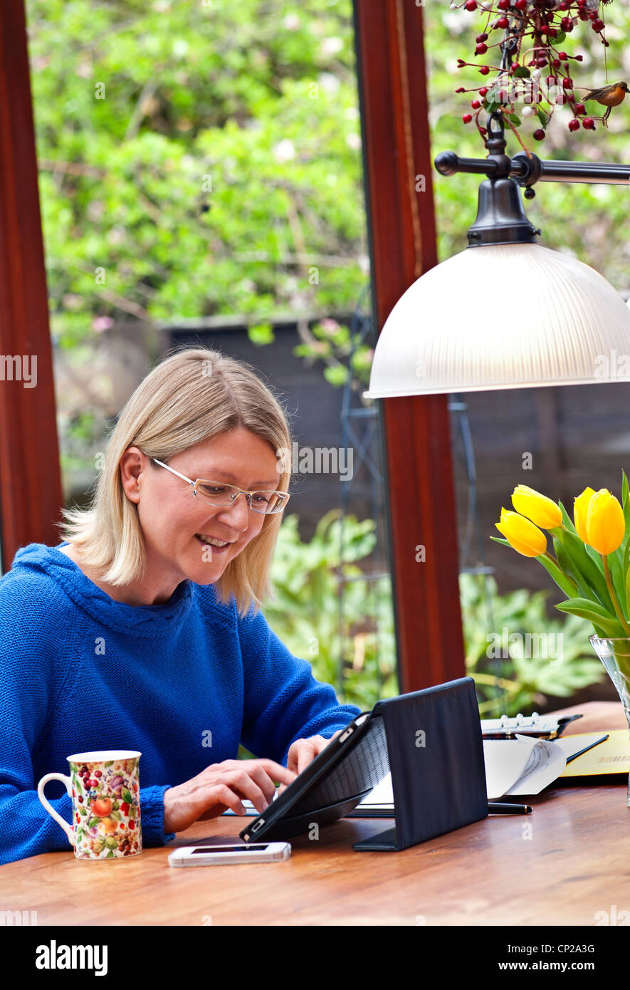 Blond woman working at home in garden conservatory using her tablet iPad computer in its leather stand cover - Stock Image