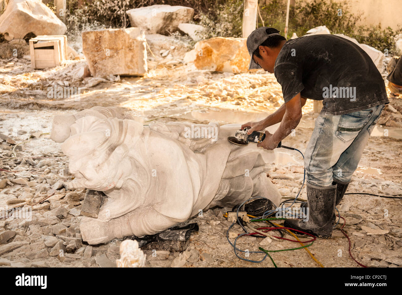 Man using an angle grinder in the manufacture of a stone statue, Tien Hieu factory, Danang, Vietnam - Stock Image
