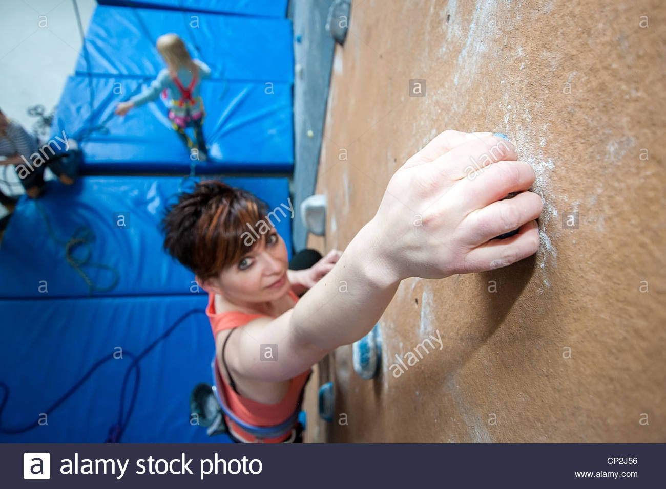 A woman climbing in an indoor climbing wall. Photo taken with a wide angle lens - Stock Image