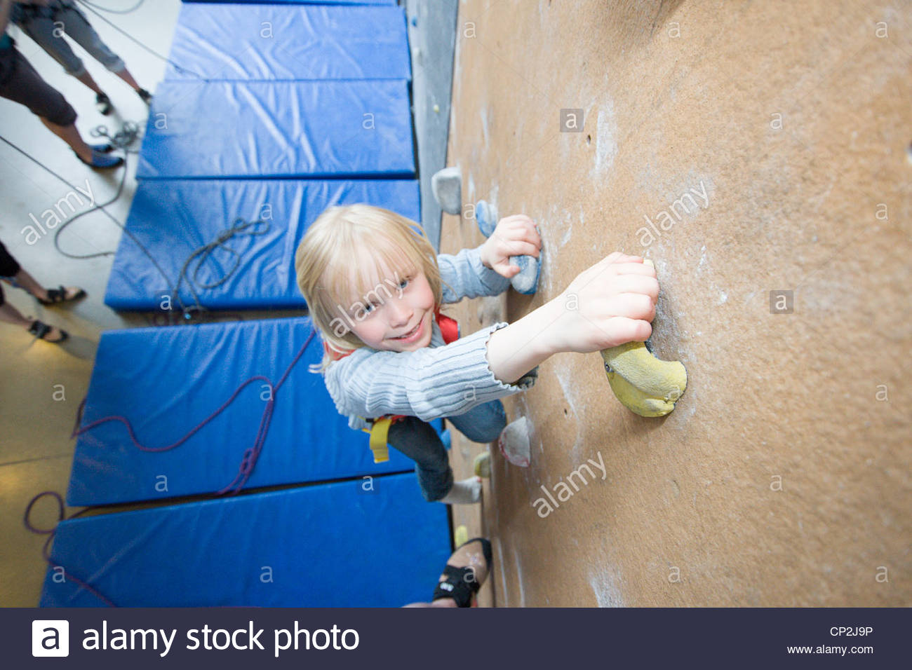 A little girl climbing in an indoor climbing wall - Stock Image