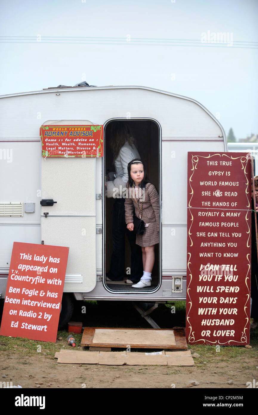 A girl peers out from the door of Fortune teller Romany Rose's caravan at the Stow-on-the-Wold horse fair May - Stock Image