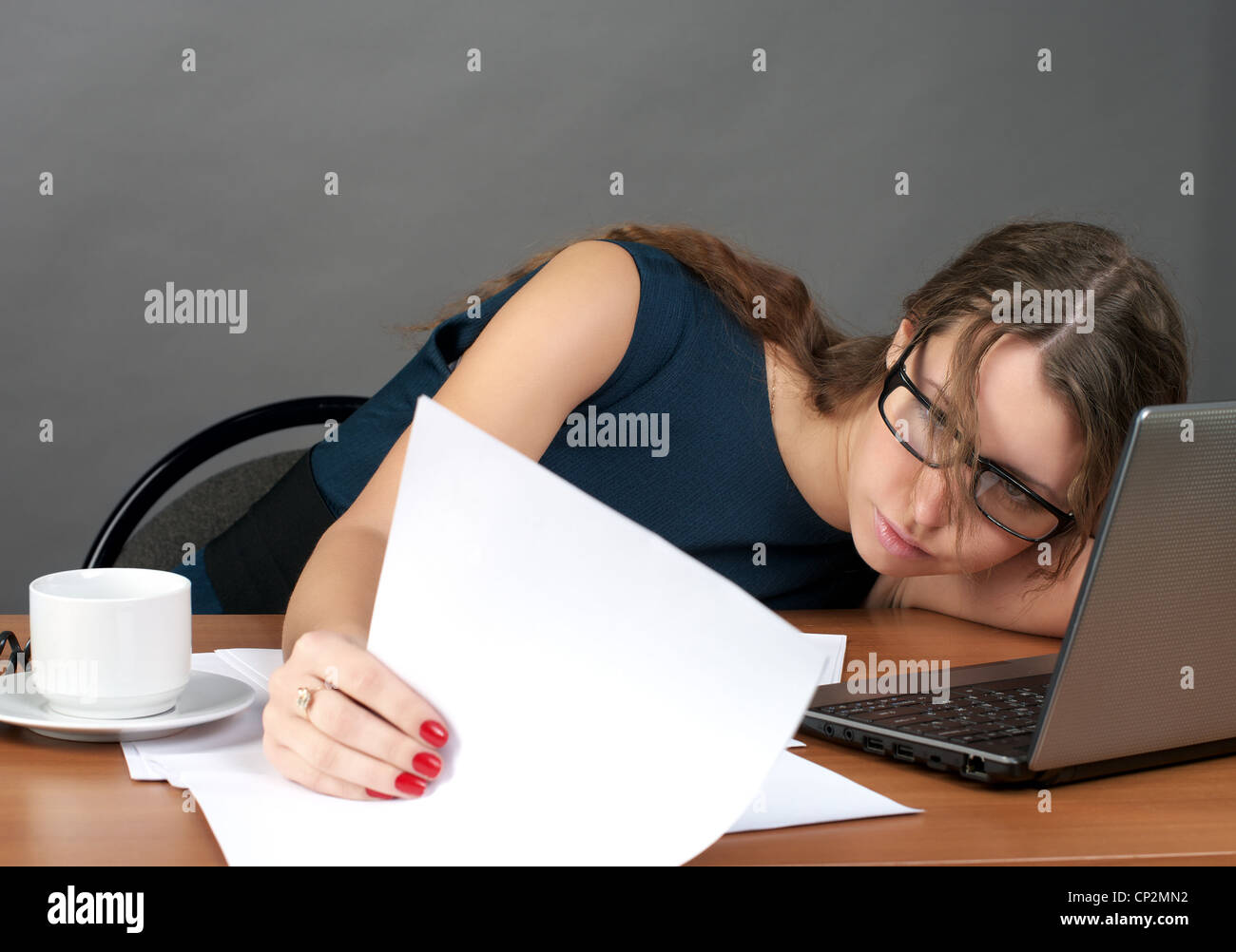 Tired businesswoman looking to the documents - Stock Image
