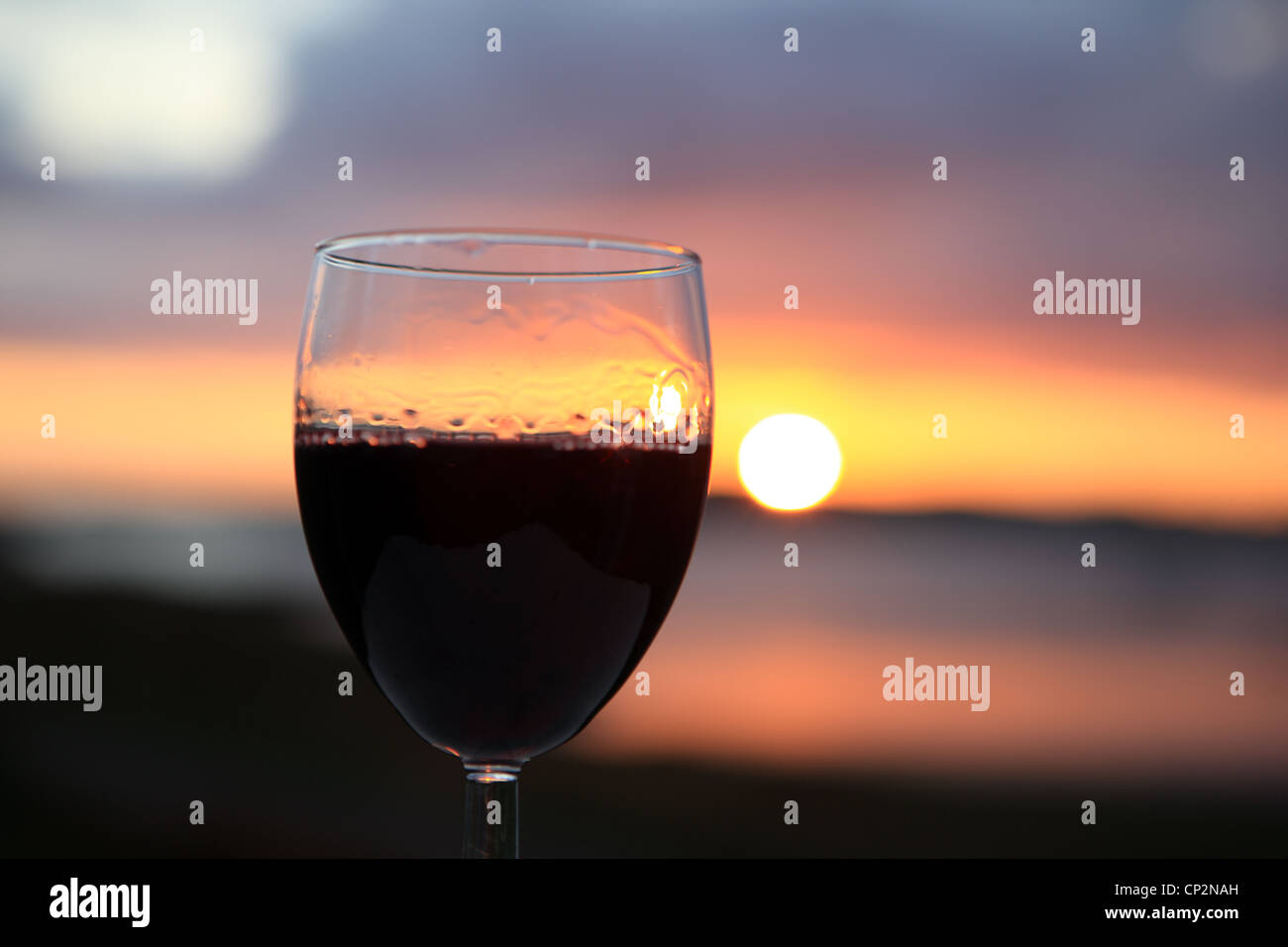 Glass of red wine against a stunning sunset - Stock Image