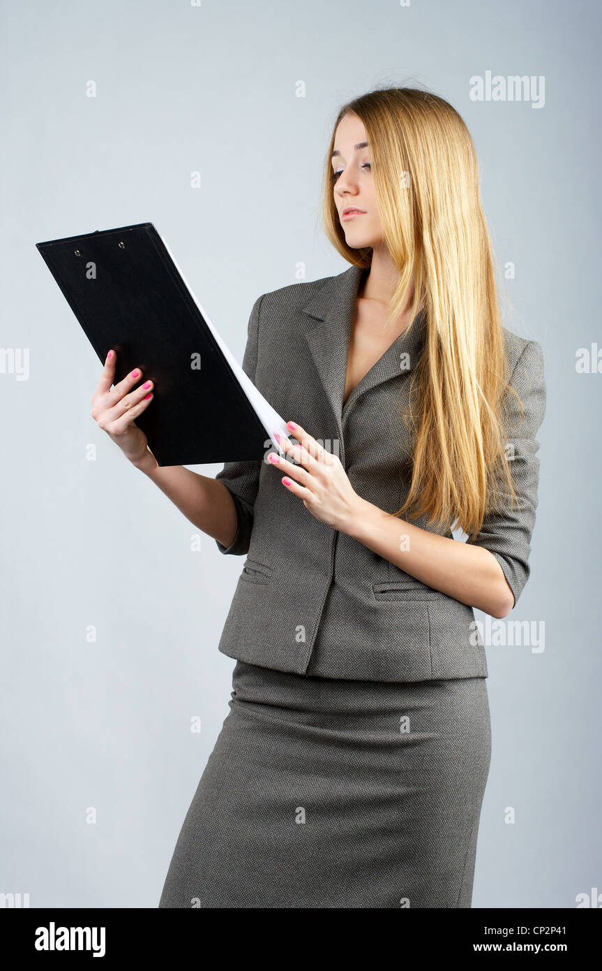 Beautiful businesswoman reads some documents in clipboard - Stock Image