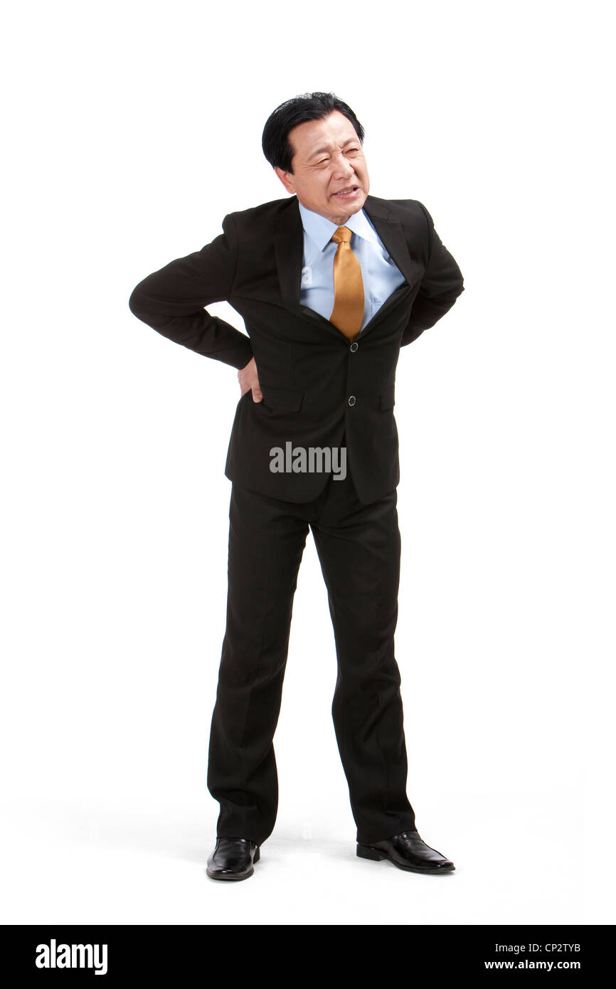 Senior businessman suffering from low back pain - Stock Image