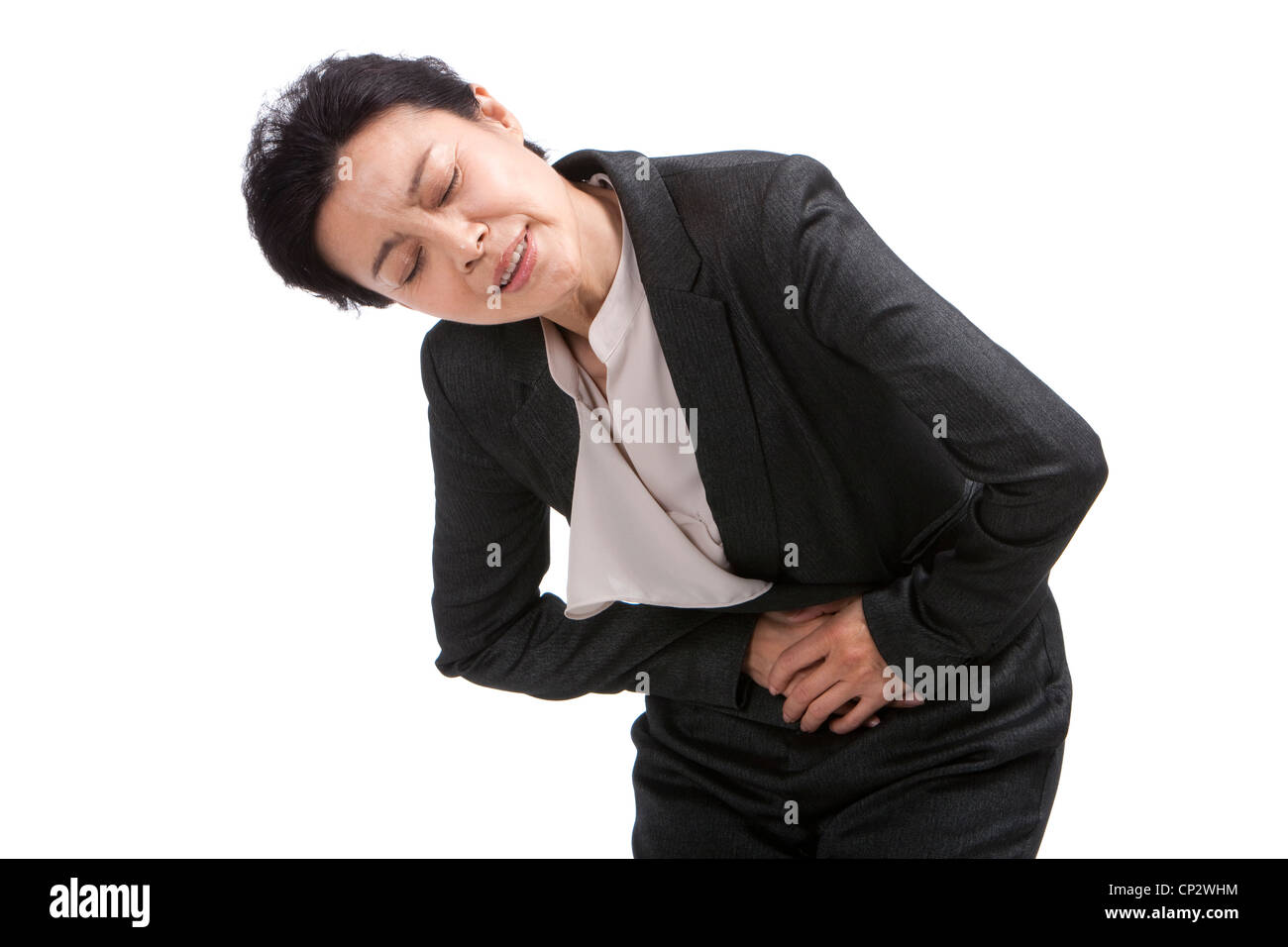 Middle-aged businesswoman suffering from stomachache - Stock Image