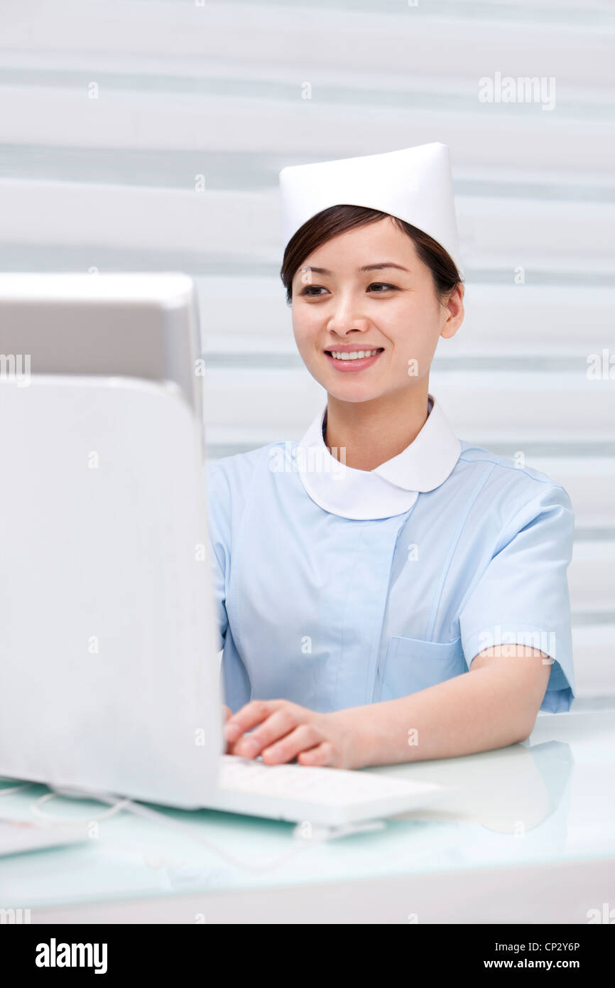 Nurse using computer in hospital - Stock Image