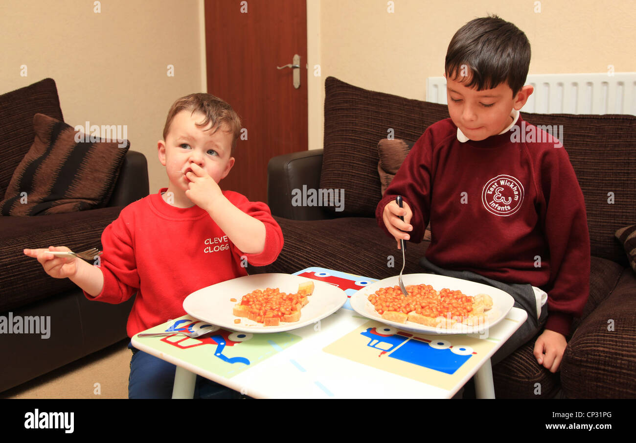 2 brothers eating dinner at a small table in the lounge after school. - Stock Image