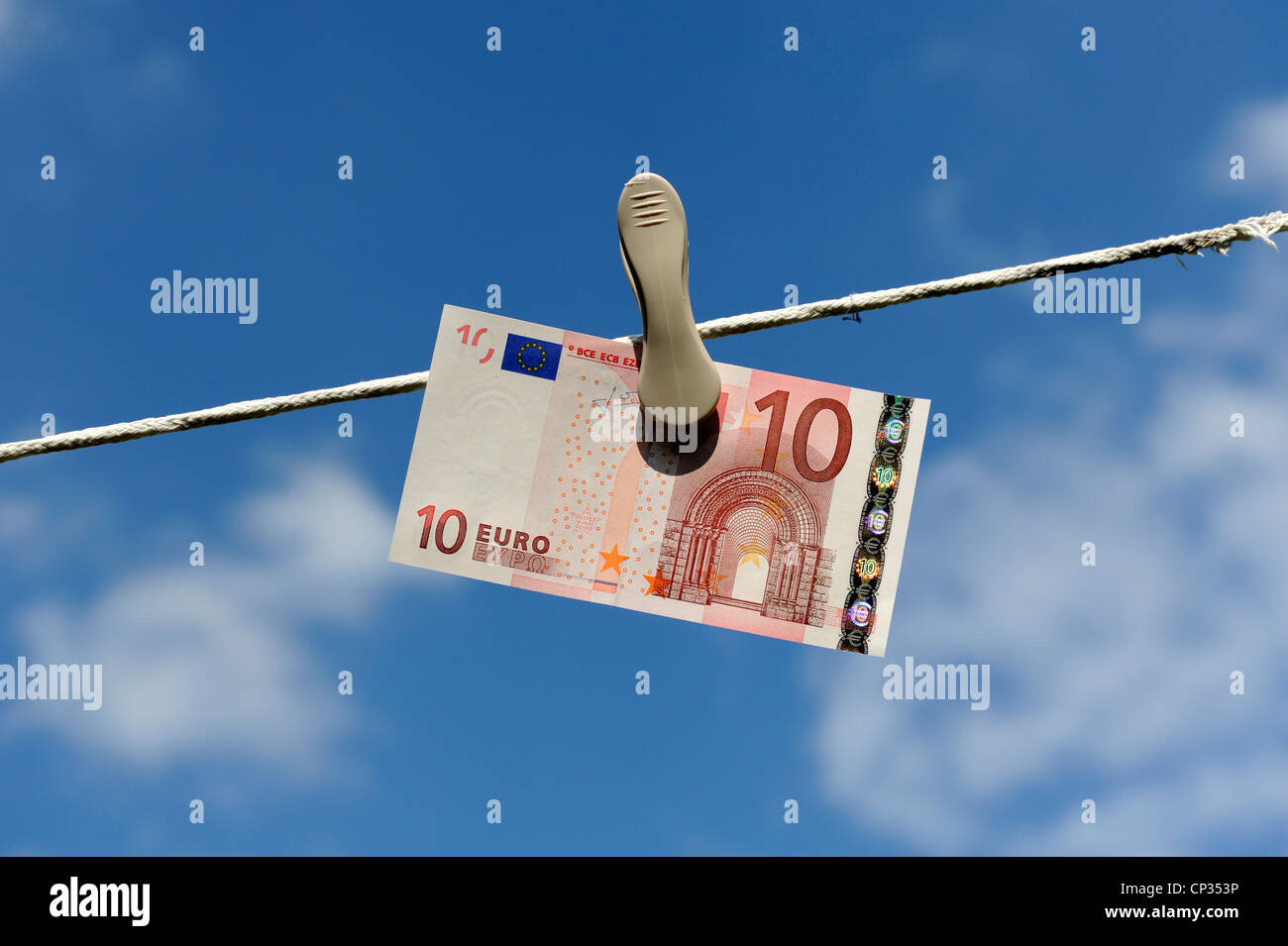 Euro note on a washing line with blue sky and clouds in the background england uk Stock Photo