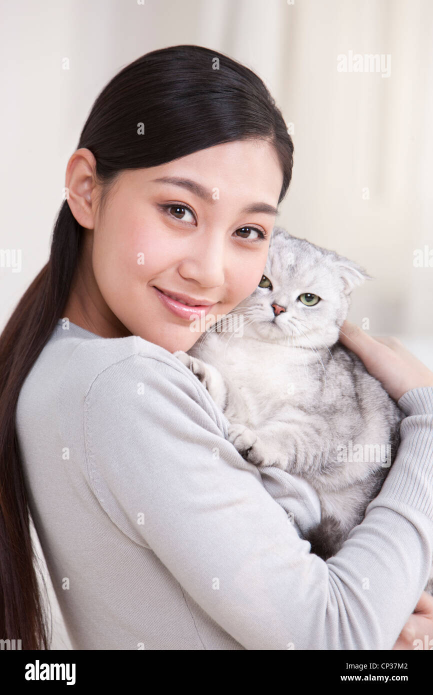 Young woman playing with a Scottish Fold cat - Stock Image
