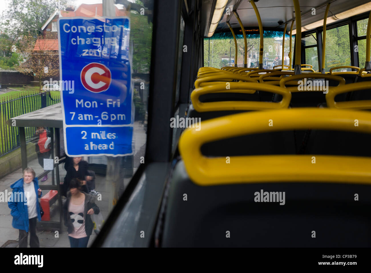 Empty top deck of London bus stopped at a bus stop with a congestion information sign. - Stock Image