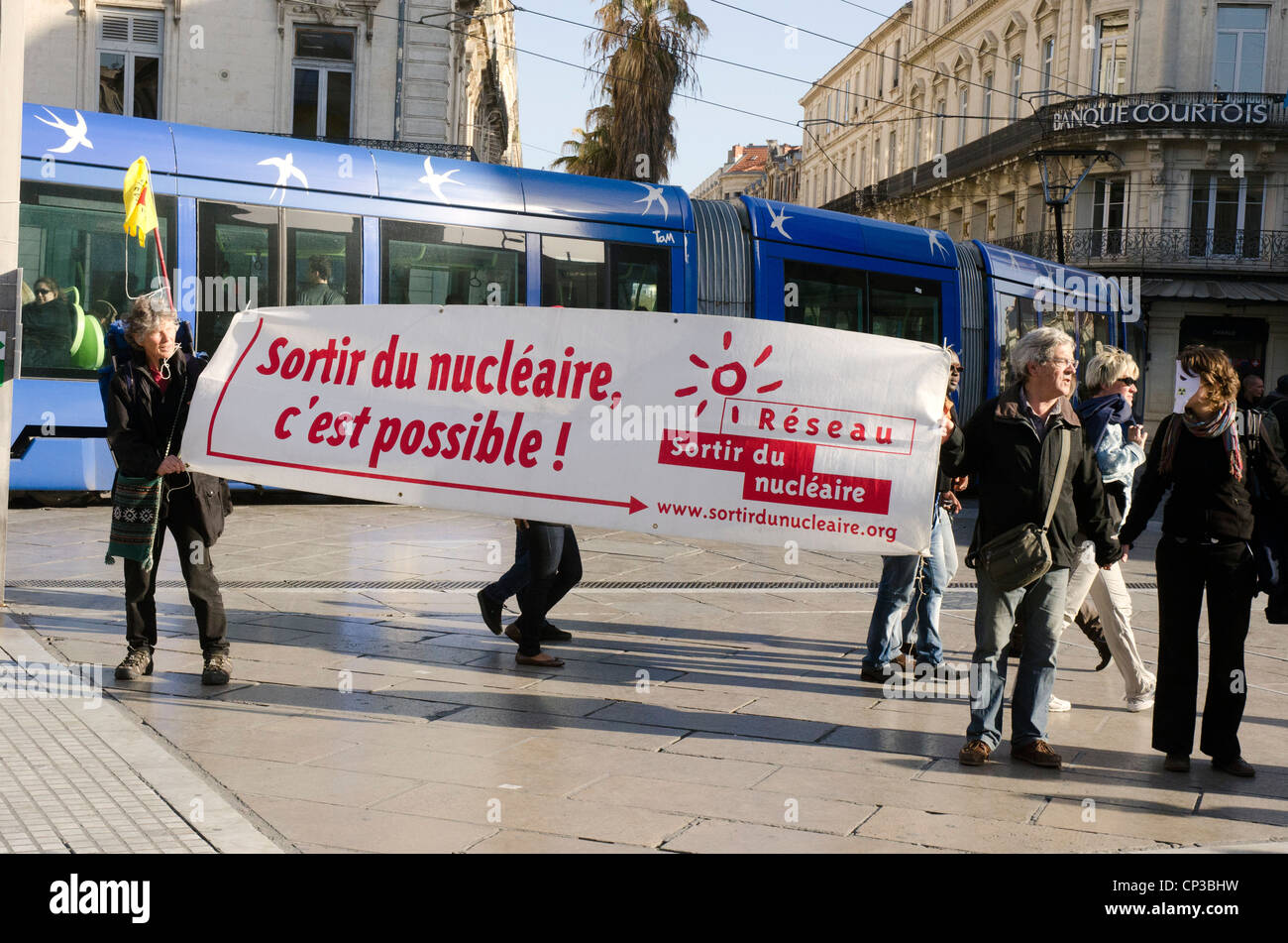 Anti-nuclear protest in the center of Montpellier with a city tram behind - Stock Image