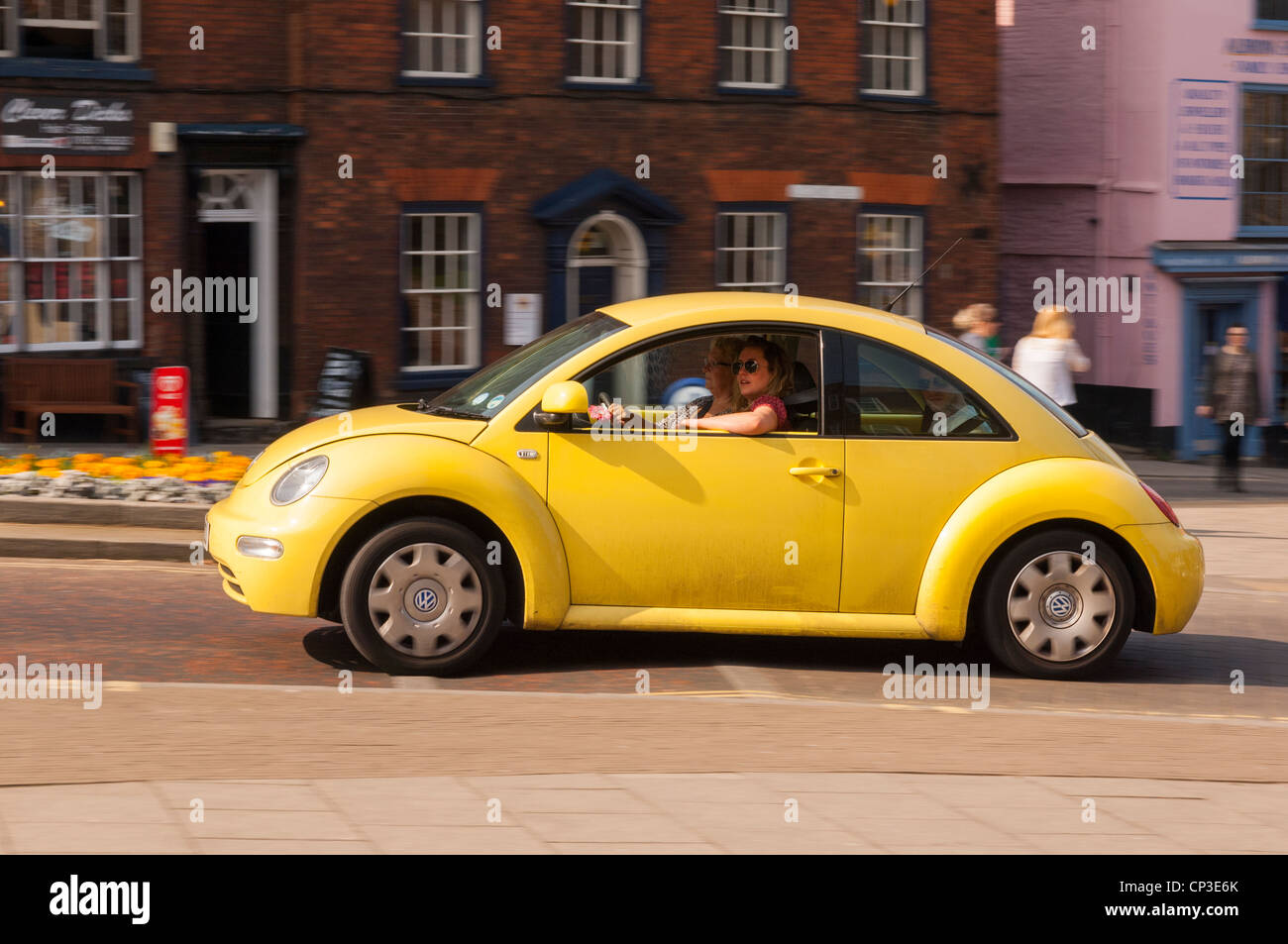 A yellow VW Beetle car driving through the city showing movement in Norwich , Norfolk , England , Britain , Uk - Stock Image