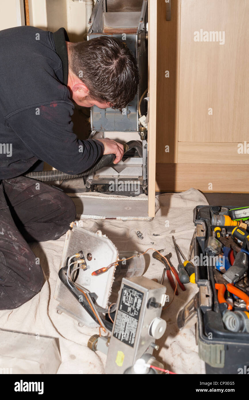 A plumbing and heating engineer servicing a gas boiler in the Uk - Stock Image