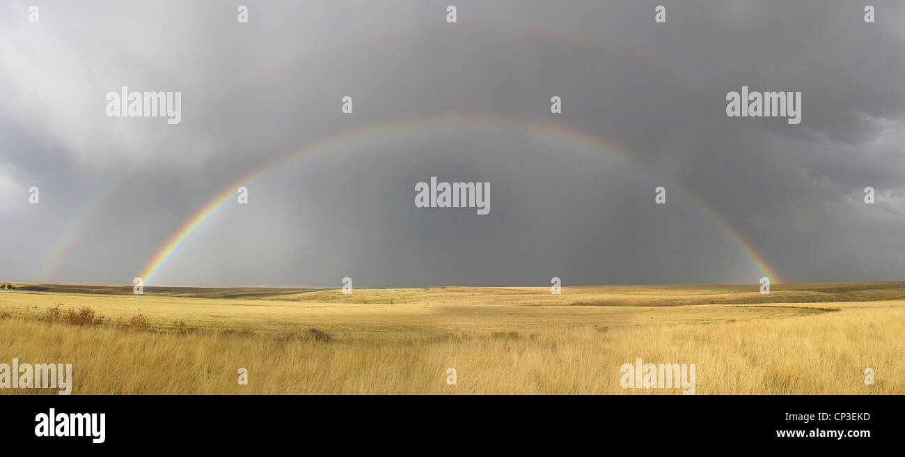 A full double rainbow appears over a large field in northeastern Oregon, USA. - Stock Image