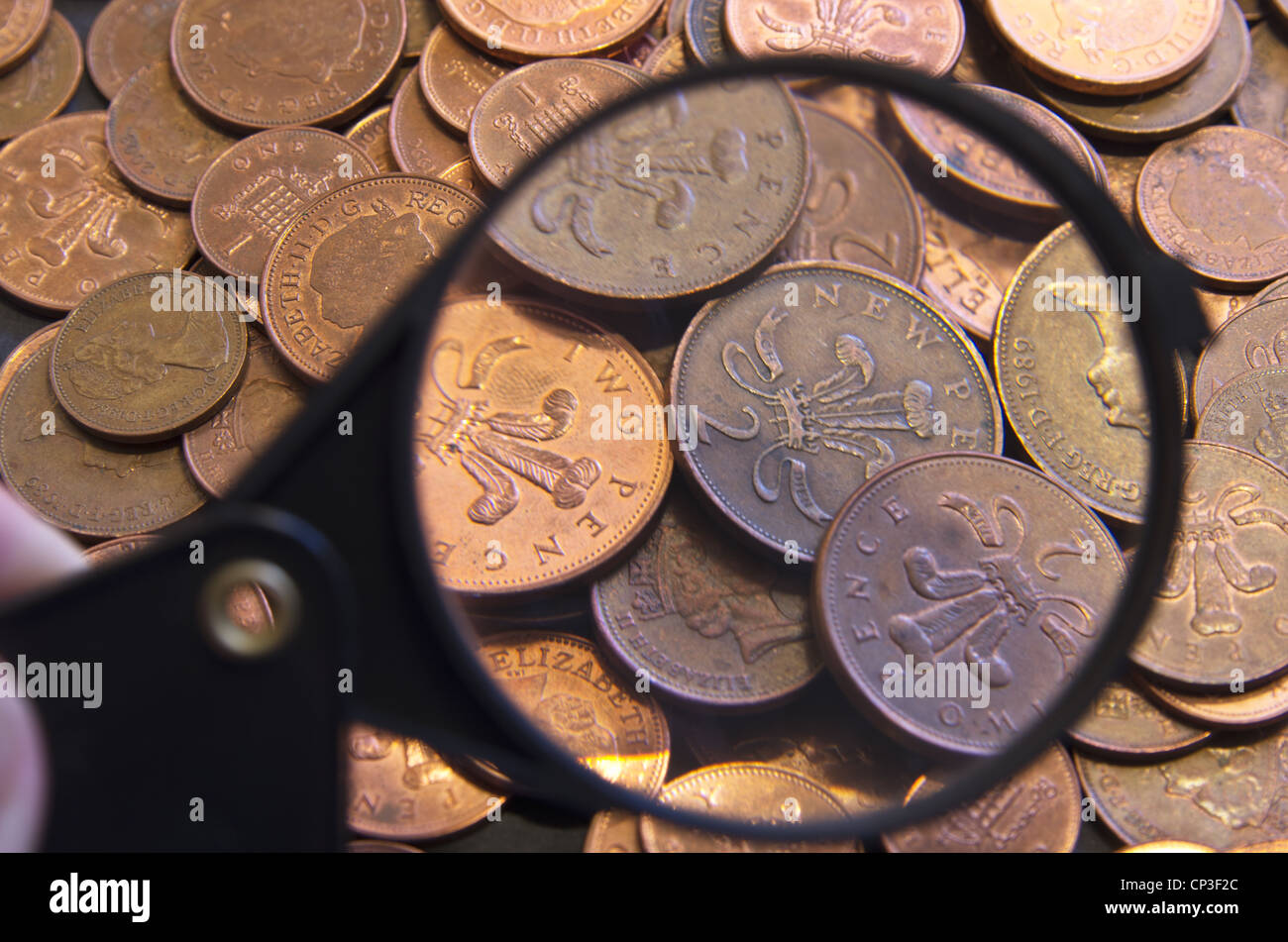 A mound of UK coins being inspected with a magnifying glass - Stock Image