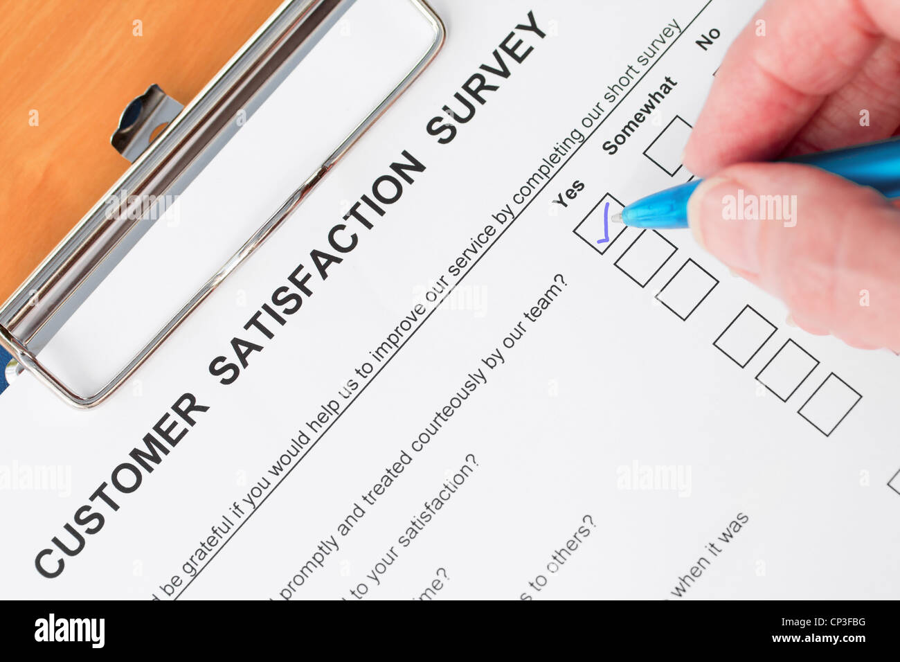 Hand Completing Customer Satisfaction Survey - Stock Image