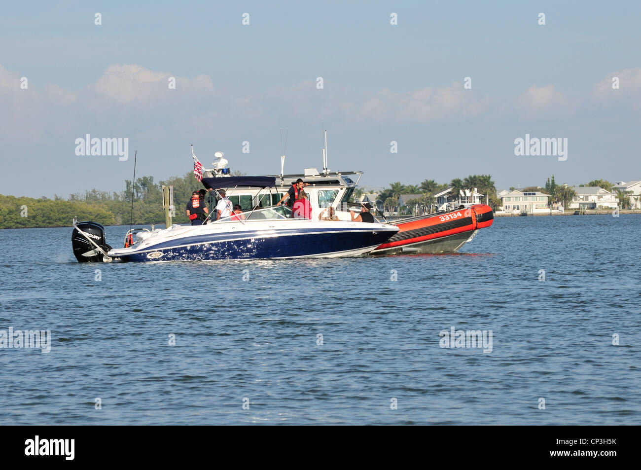 A coast guard boat tows a disabled boat near Fort Myers Beach, Florida - Stock Image