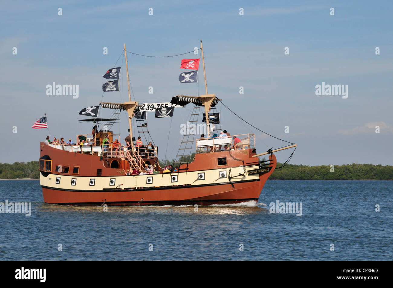 Pieces of Eight, a faux pirate ship, heads back to port in Fort Myers Beach carrying a load of happy visitors - Stock Image