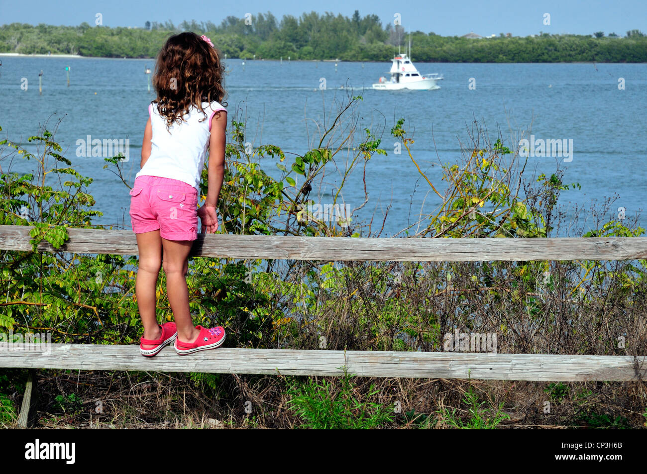 Young girl stands on a fence rail to get a better view of boats passing Bowditch Park, Ft. Myers Beach, Florida - Stock Image
