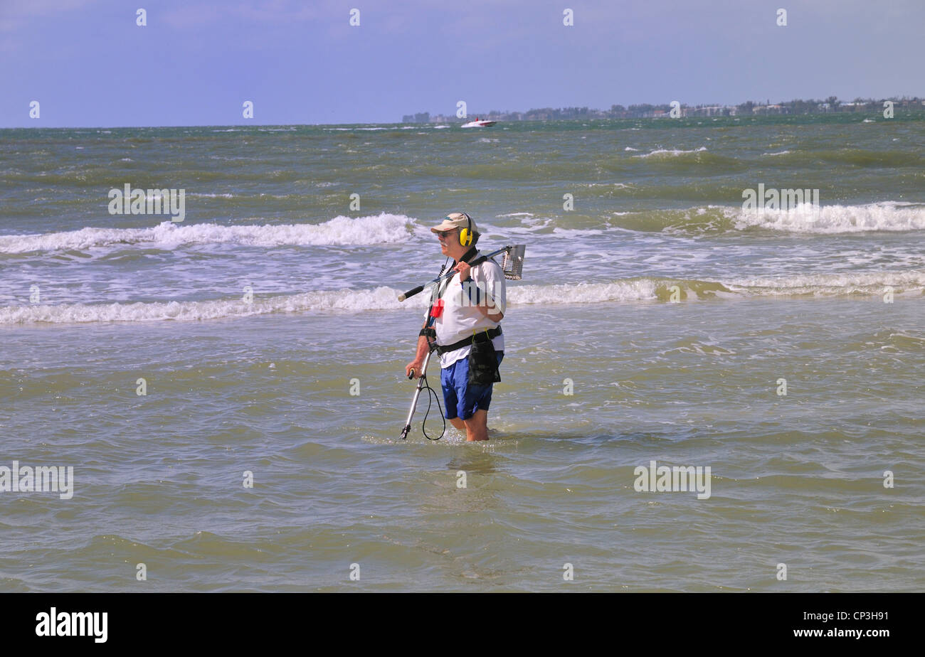 Armed with a metal detector and a strainer, a man searches a shallow beach area for treasure - Stock Image