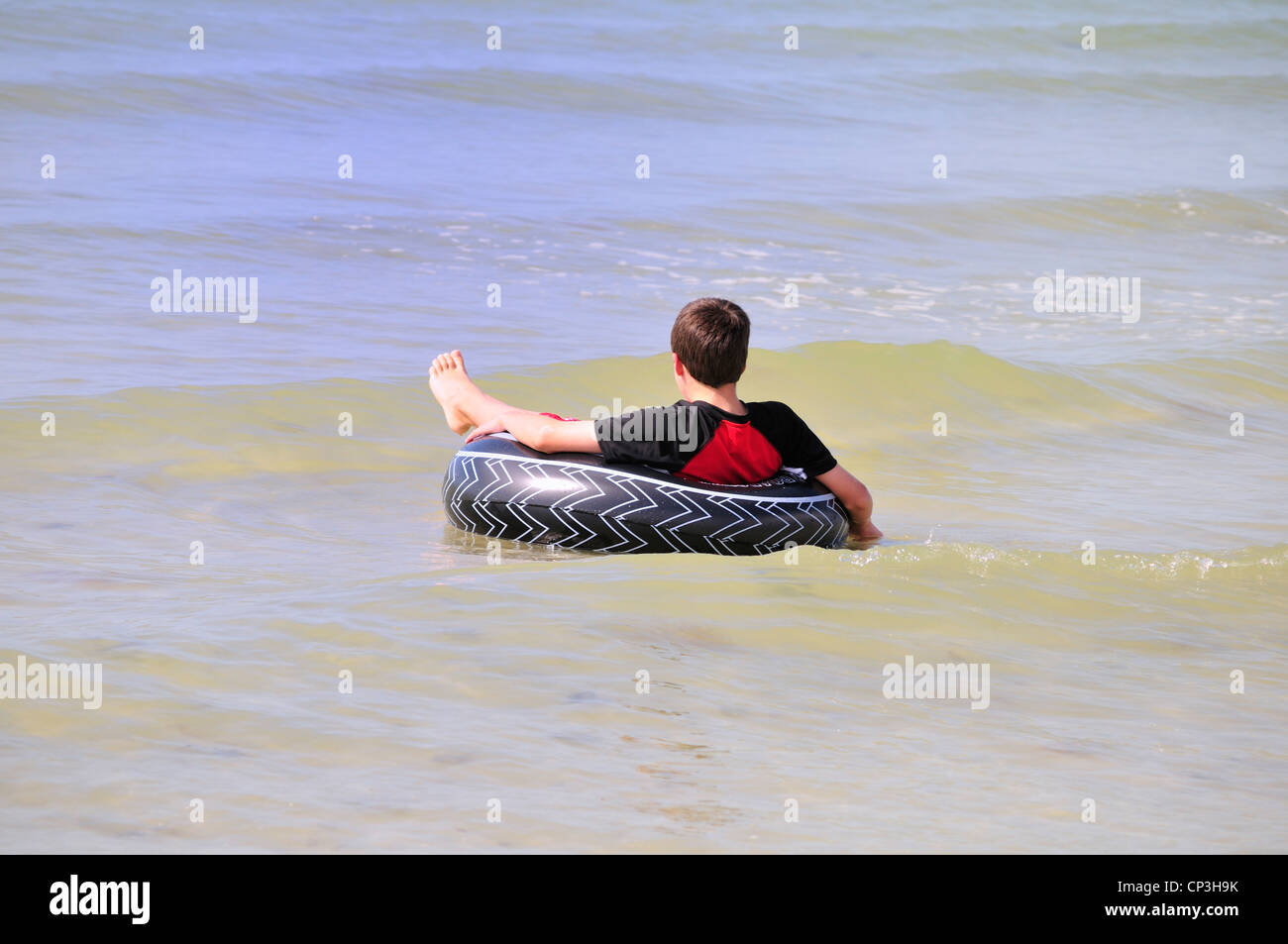 Boy relaxing in an inner tube at Fort Myers Beach - Stock Image