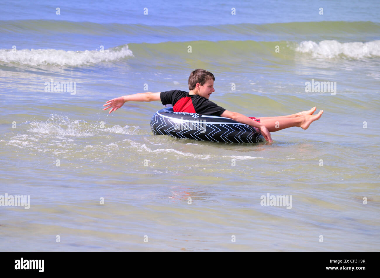 Boy spinning in an inner tube at Fort Myers Beach - Stock Image