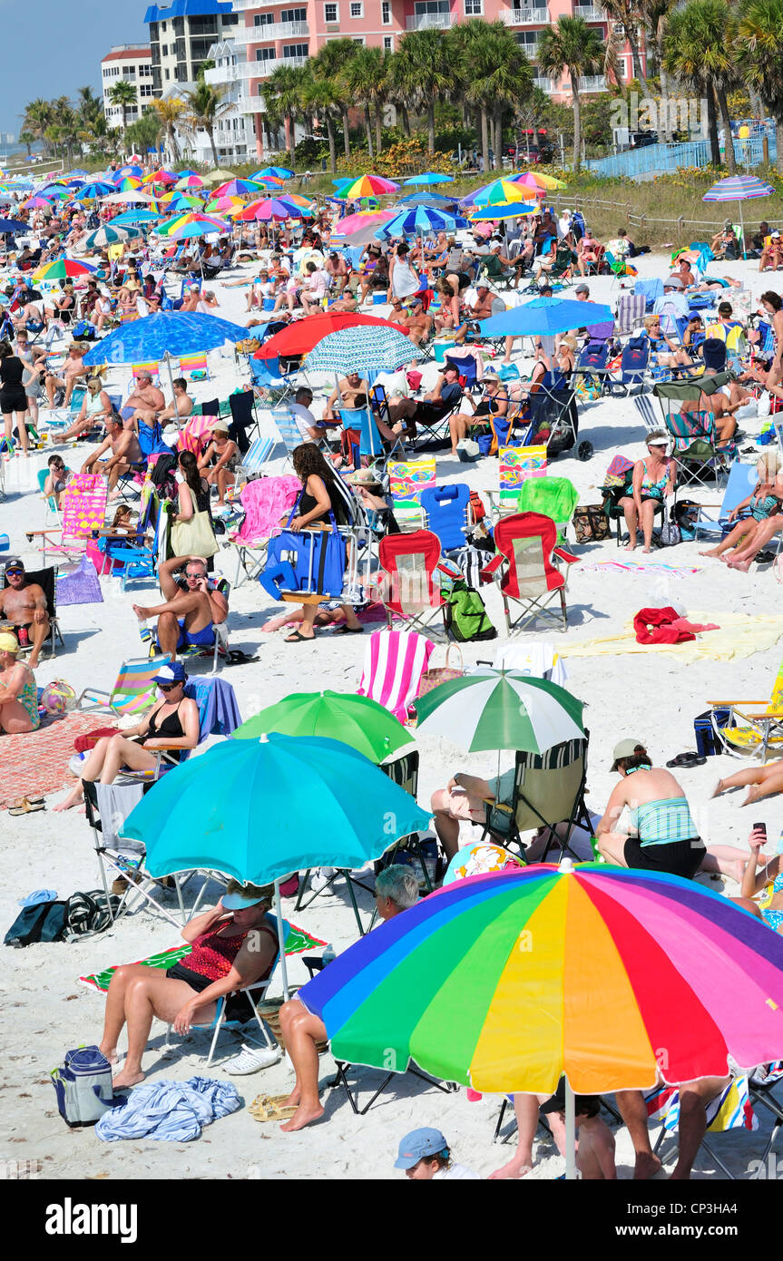 Colorful umbrellas and people crowd Fort Myers Beach, Florida - Stock Image
