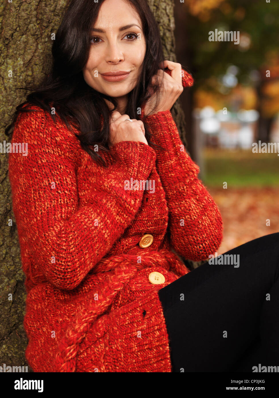 Beautiful smiling young woman cuddling up in a red sweater outdoors in fall Stock Photo