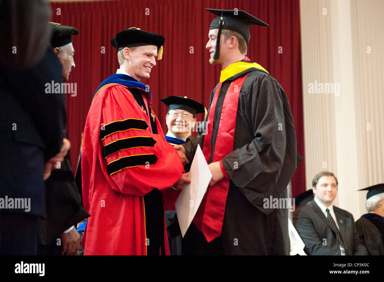 Male student receiving diploma at college graduation - Stock Image