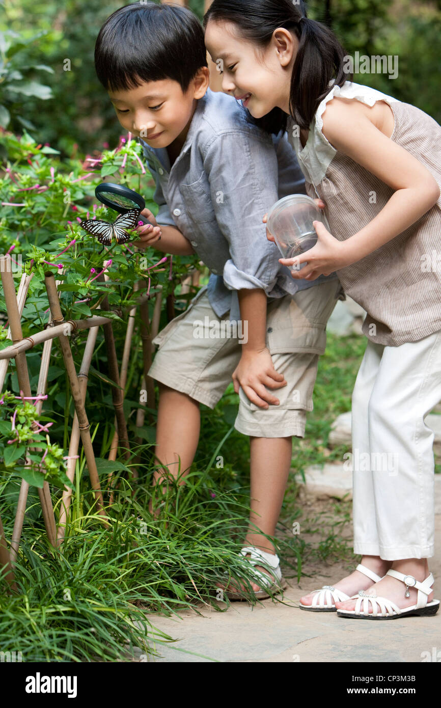 Chinese children in a garden looking at a butterfly - Stock Image