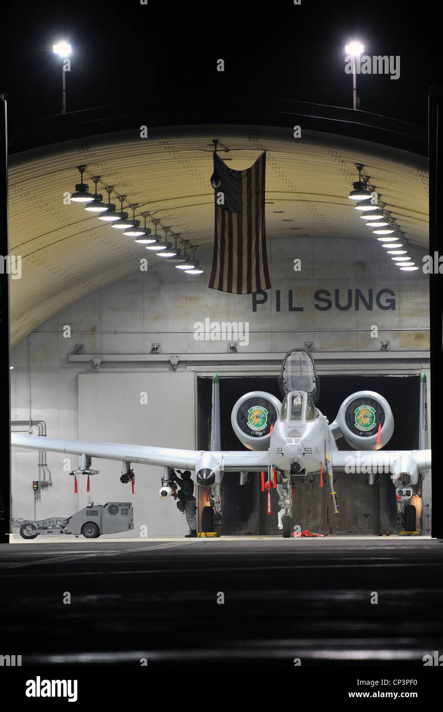An A-10 Thunderbolt II sits inside a hardened aircraft shelter awaiting weapons loading during Beverly Midnight - Stock Image