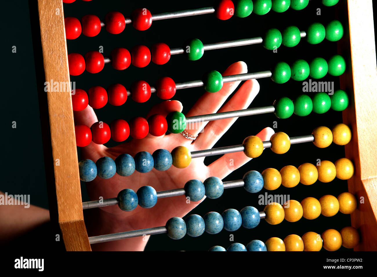 abacus with hand on a dark background - Stock Image