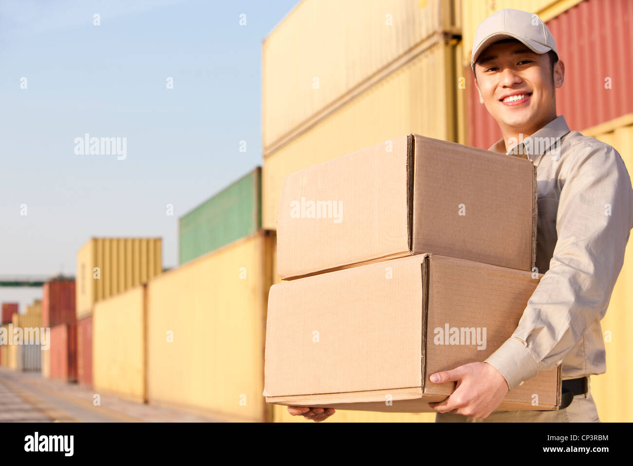 shipping industry worker carrying cardboard boxes - Stock Image