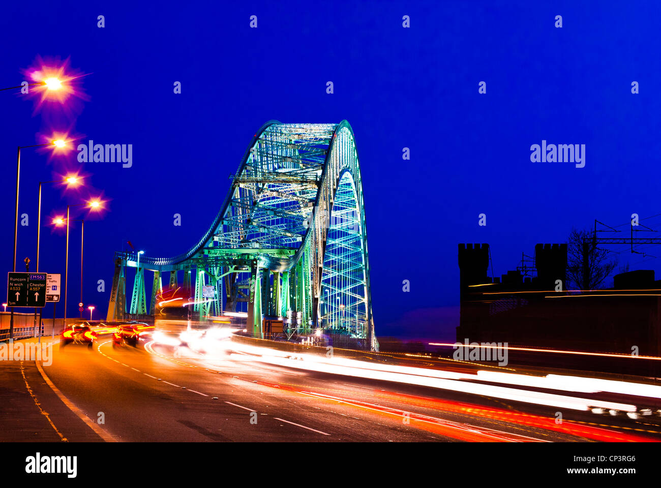 Car traffic light trails crossing The Silver Jubilee Bridge, Runcorn at night, Cheshire, England, UK - Stock Image